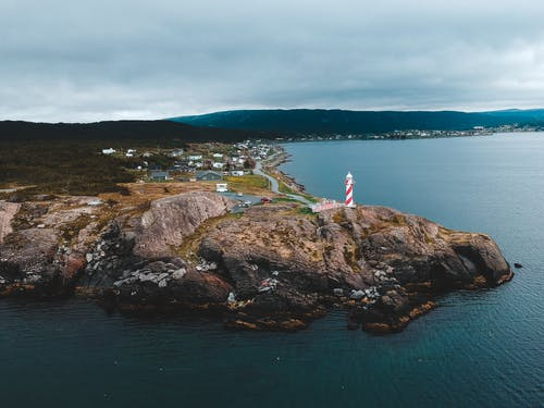 Cloudy sky over rocky seashore with lighthouse and residential houses
