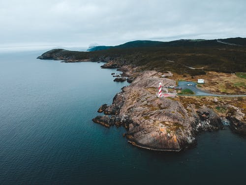 Majestic drone view of rippling ocean with lighthouse on rocky coast against cloudy sky