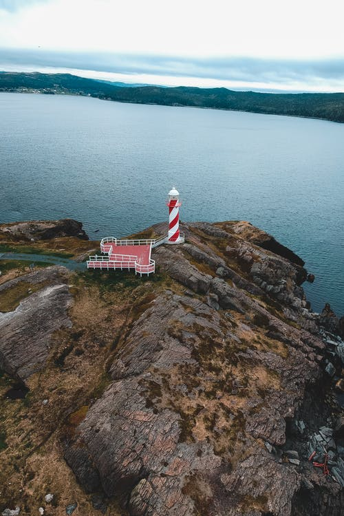 Drone view of colorful striped beacon near observation deck on bristly mount near ocean under cloudy sky