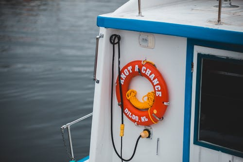 Modern small vessel with red lifesaver ring on wall floating on rippling river water in daylight