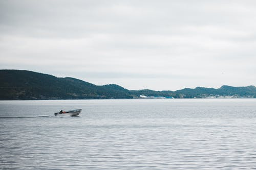 Small powerful motorboat floating fast on tranquil rippling sea surface against green hilly coast on overcast weather