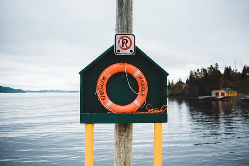Colorful stand with red lifebuoy located on quay near peaceful rippling pond in countryside on cloudy day