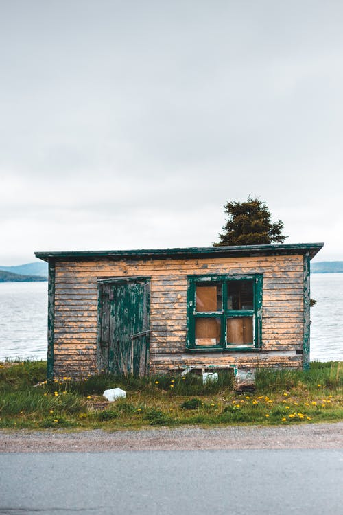 Exterior of shabby desolated wooden cottage located on grassy seacoast under gray overcast sky