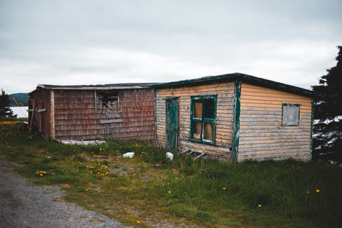 Exterior of obsolete abandoned cottages with wooden shabby walls located on grassy riverside against gloomy overcast sky