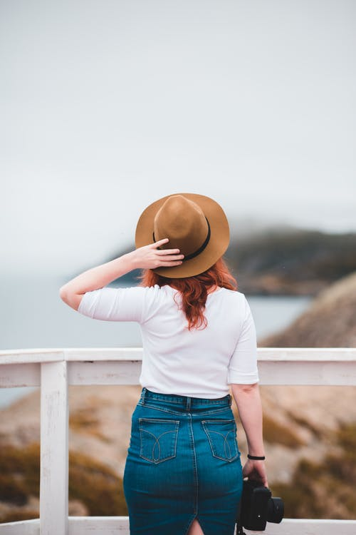 Back view faceless female traveler in casual outfit standing near waterfront railing and touching hat while enjoying views of blurred rough seashore