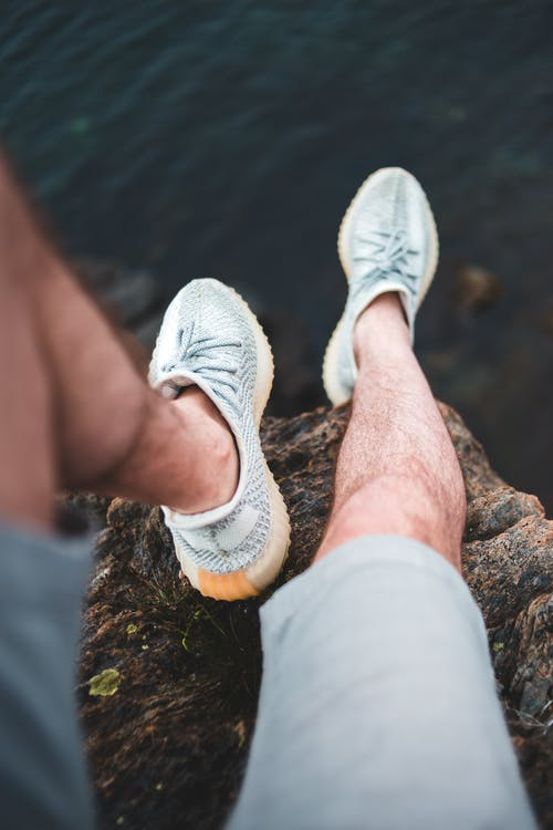 From above crop anonymous male legs in sneakers and shorts resting on rough rock above calm rippling sea