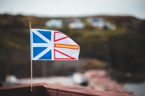 Waving national flag of Newfoundland and Labrador placed on wooden fence against blurred coastal settlement on hilly terrain