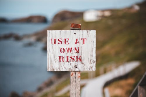 Sign with text Use At Own Risk on rocky seacoast