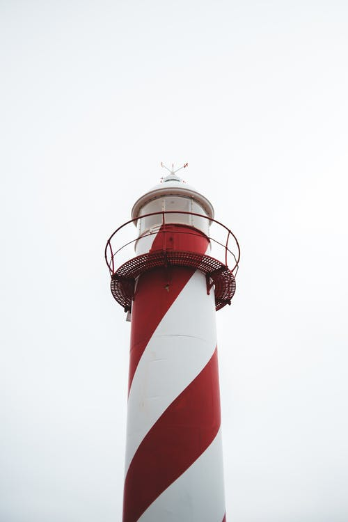 From below of white and red lighthouse with observation deck against cloudy sky