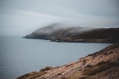 Rocky coastline of rippling ocean against misty sky