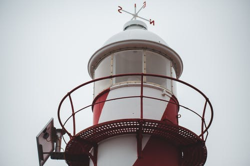 Low angle of white and red lighthouse tower with windrose on domed roof against overcast sky