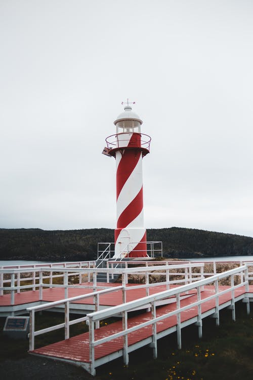 From below of lighthouse tower with red and white colors located on rocky shore of sea against cloudy sky