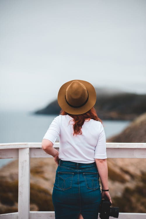 Stylish woman admiring view of sea in mountains on cloudy day