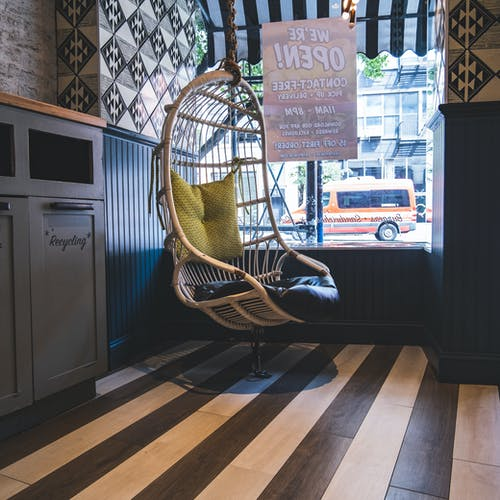 Interior of cozy cafe with wicker hanging egg chair with pillows near window