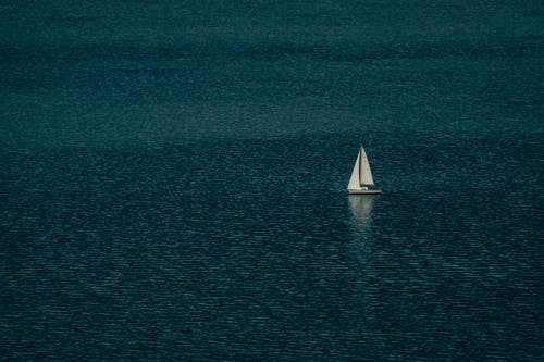 Lonely boat with white sails floating on surface of rippling endless blue sea on sunny day
