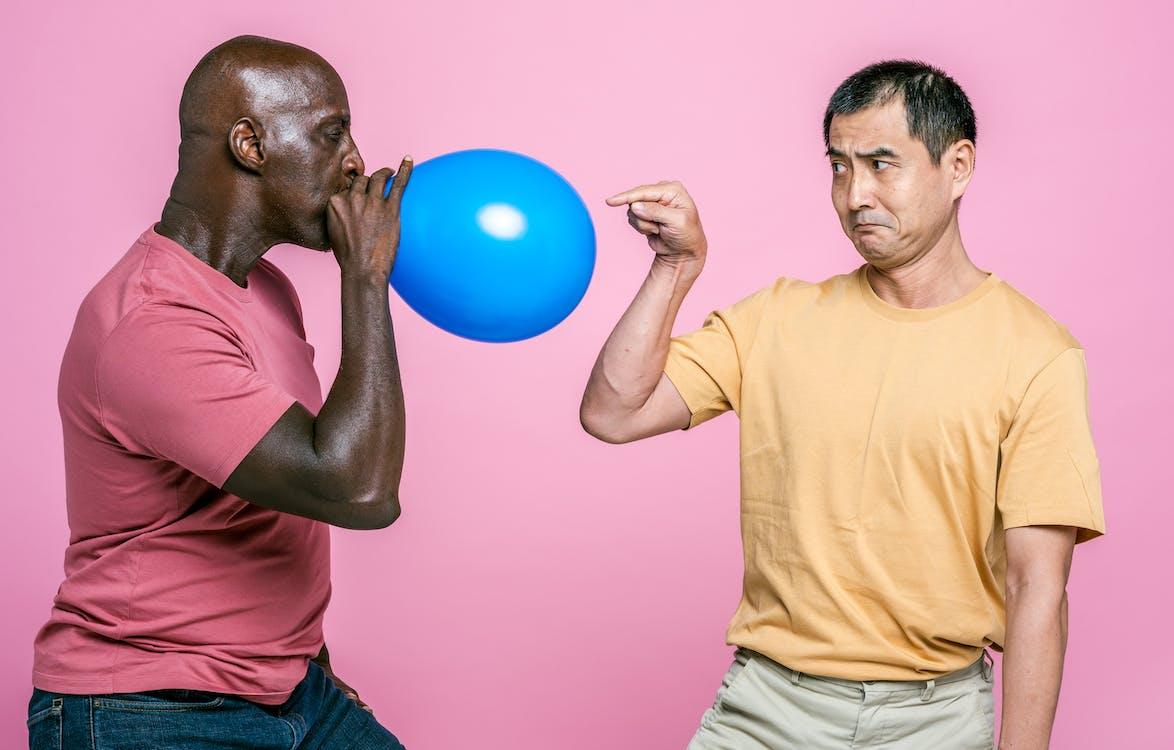Man in Yellow Crew Neck T-shirt Holding Blue Balloon
