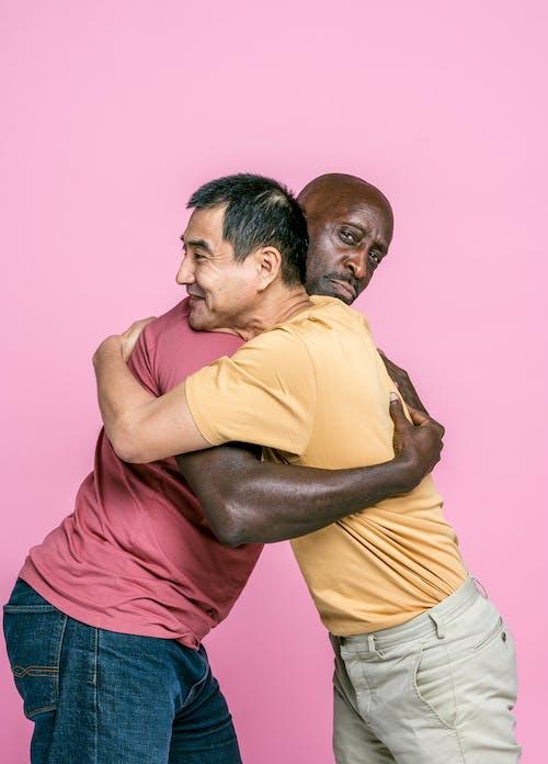 Man in Yellow Polo Shirt Hugging Woman in Pink Shirt