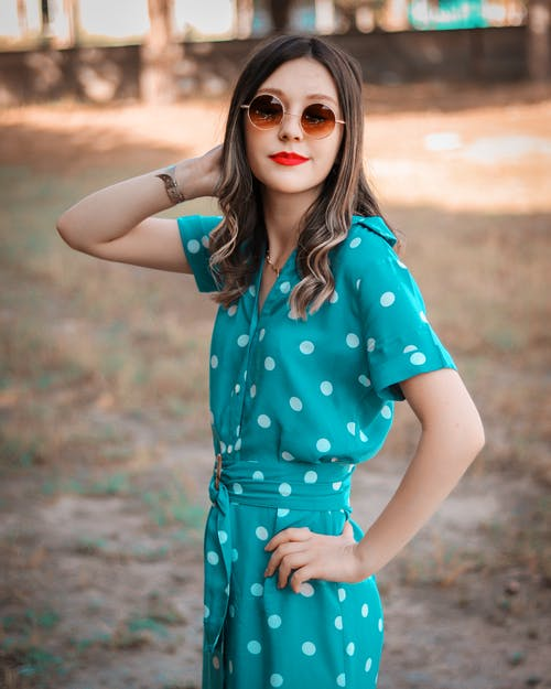 Side view of positive young female in trendy dress and sunglasses touching hair while resting in countryside on sunny day