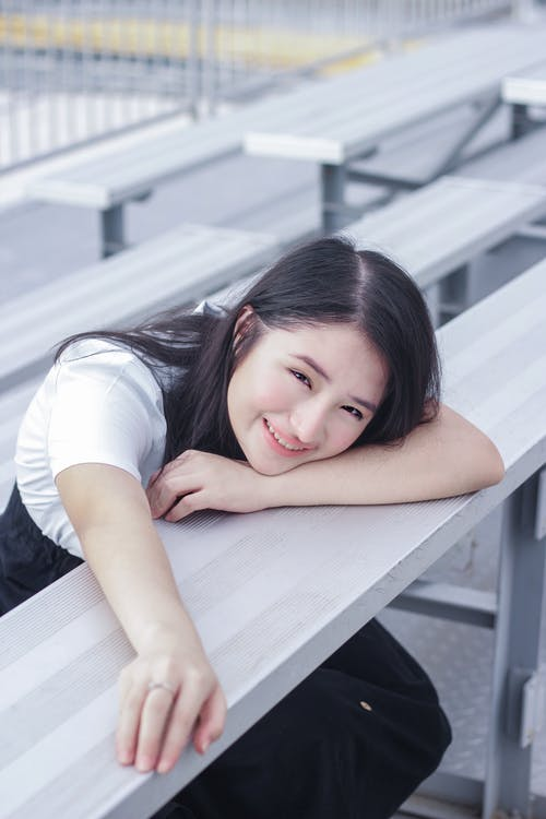 Positive ethnic female teenager resting at table