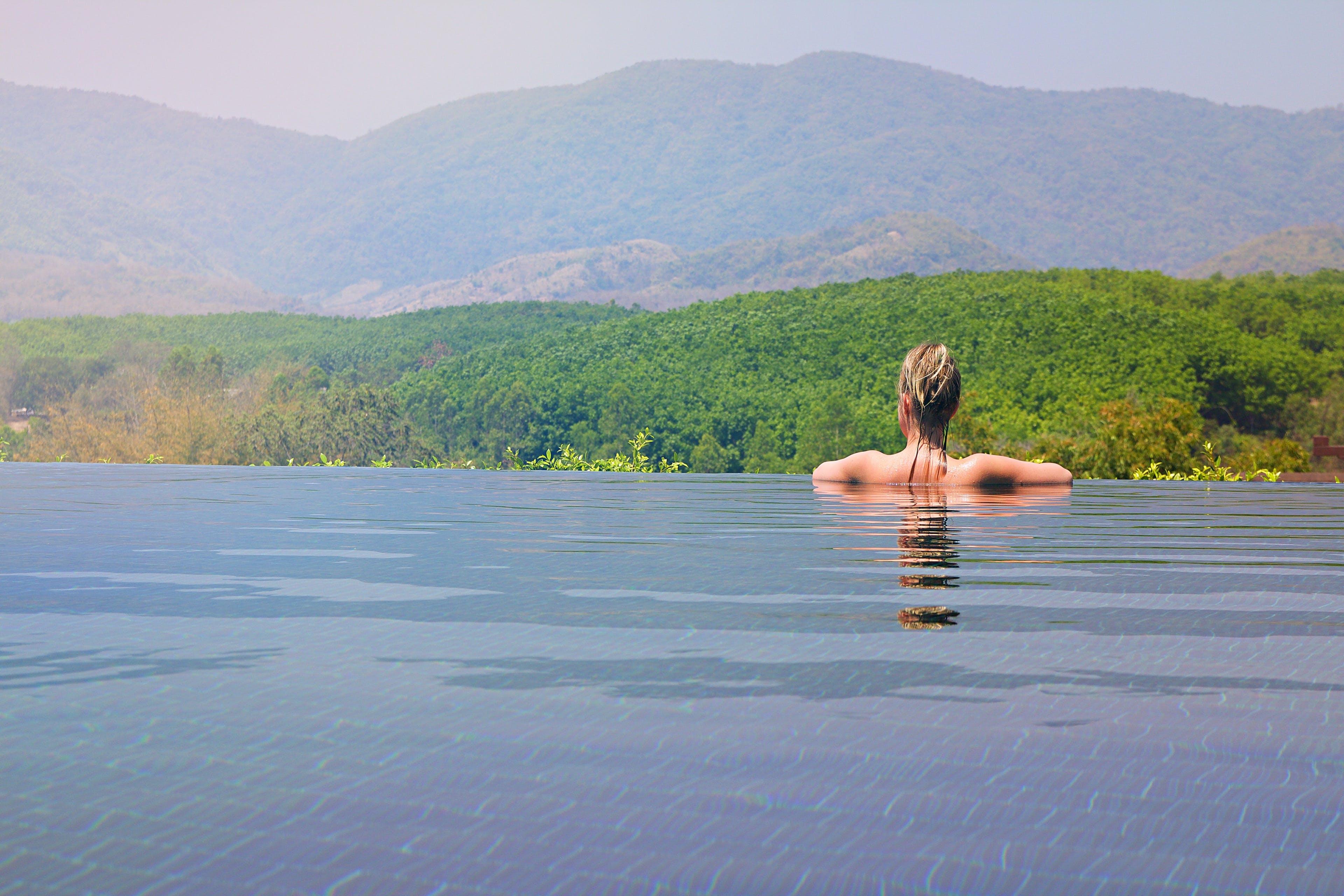 Woman Half Submerge Facing on Mountain