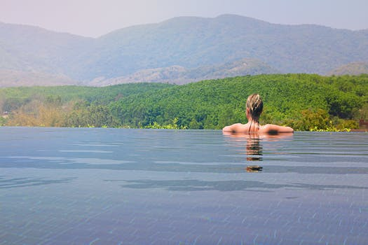 A swimmer looking across a forest, mountain ranges to the sky beyond to signify outlook