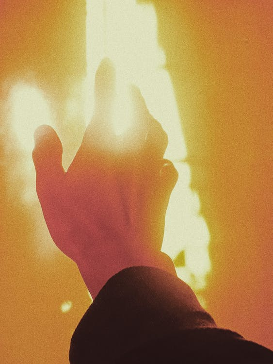 Anonymous person reaching out hand to fire