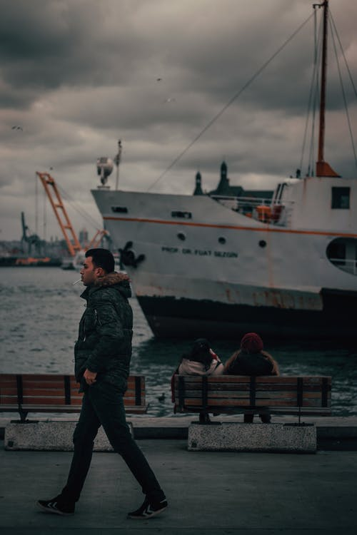 Side view of young male tourist in warm clothes walking on embankment near rippling river with moored ships against dramatic cloudy sky