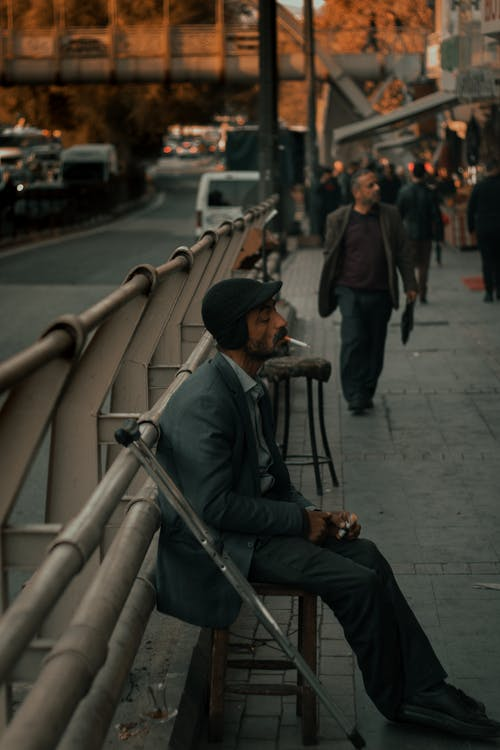 Side view of middle aged thoughtful ethnic male in casual clothes with crutches sitting on stool on street and smoking
