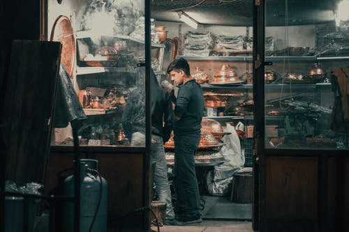 Young ethnic man working in traditional oriental store