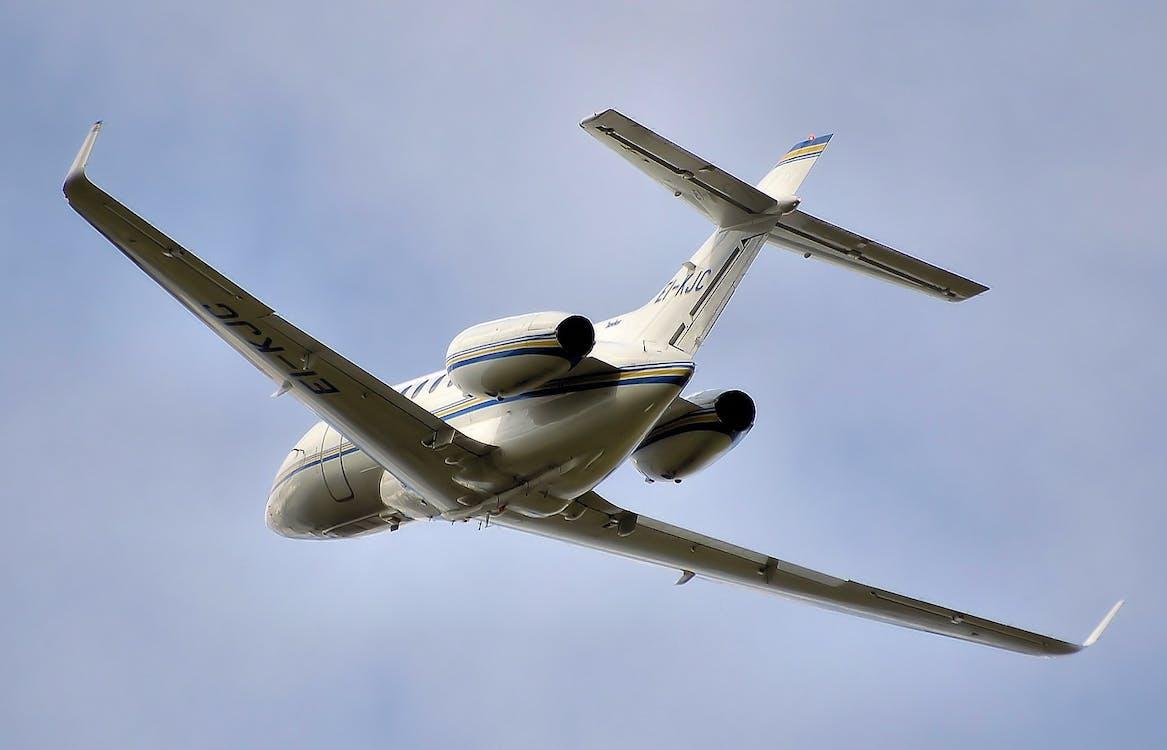 White Passenger Plane Flying Under Blue Sunny Cloudy Sky