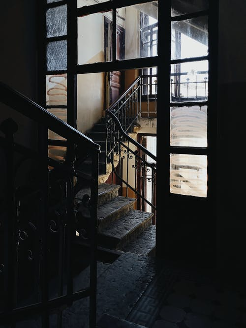 Stairwell interior inside of ancient historical residential building with metal railings and weathered steps