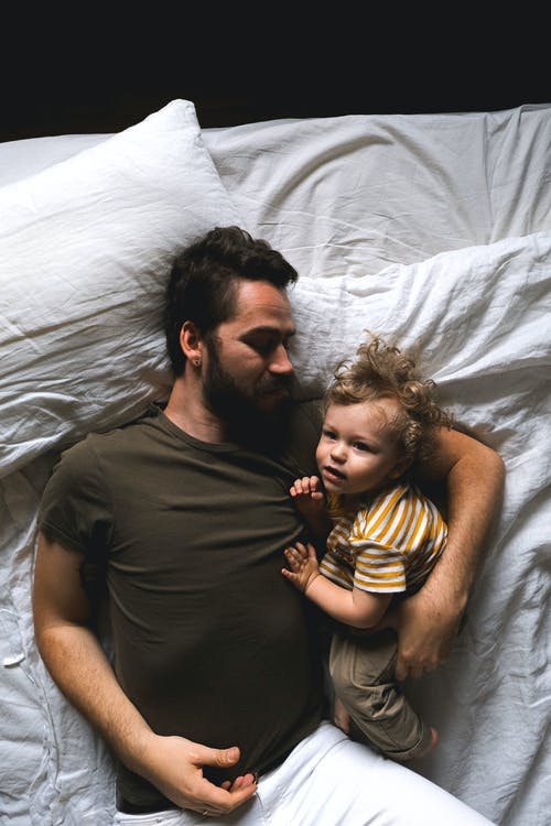 Man and Son Lying in Bed
