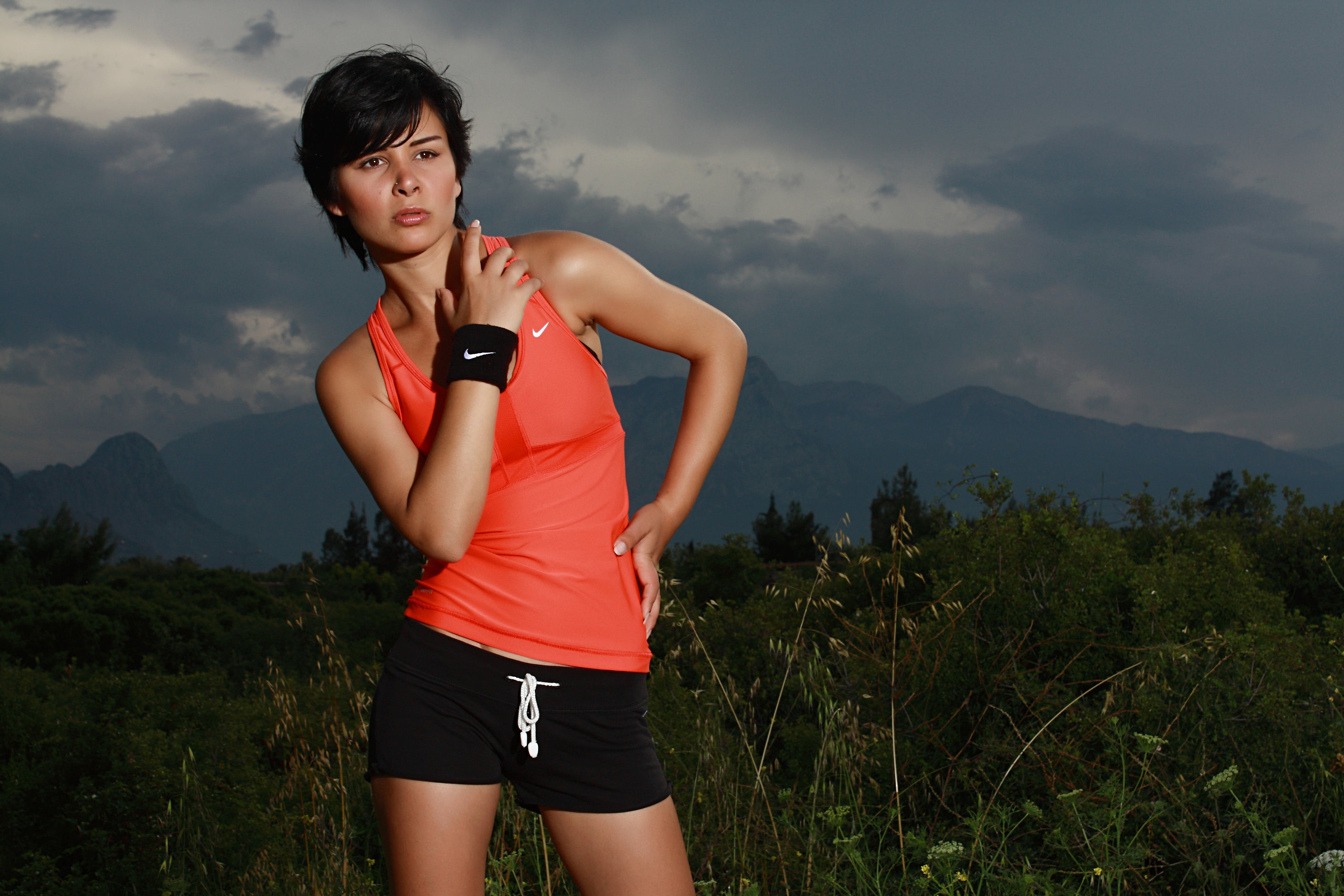 Woman in Orange Nike Tank Top Surrounded With Grasses
