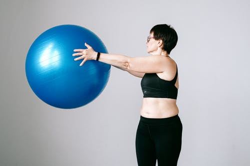 Woman in Black Sports Bra and Black Leggings Holding Blue Exercise Ball