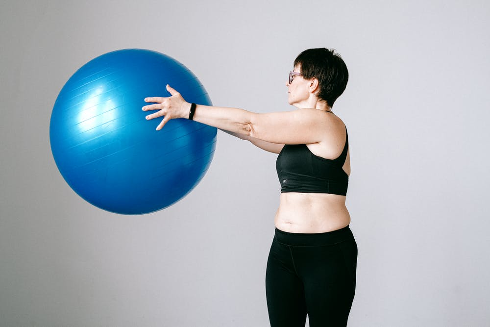 Woman holding blue exercise ball. | Photo: Pexels