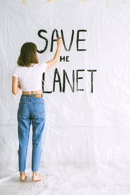 Woman in White Shirt and Blue Denim Jeans Standing in Front of White Wall