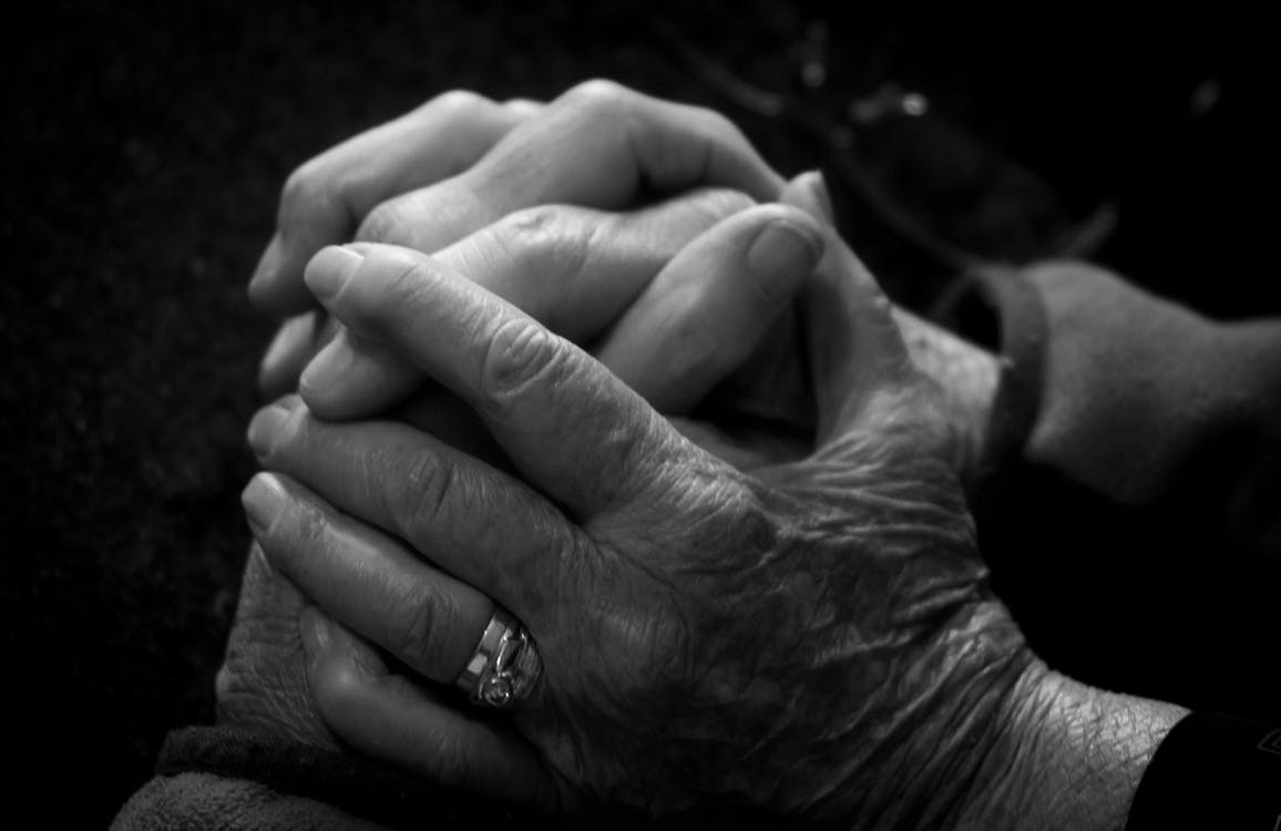 Grayscale Photo of Persons Hand With Ring