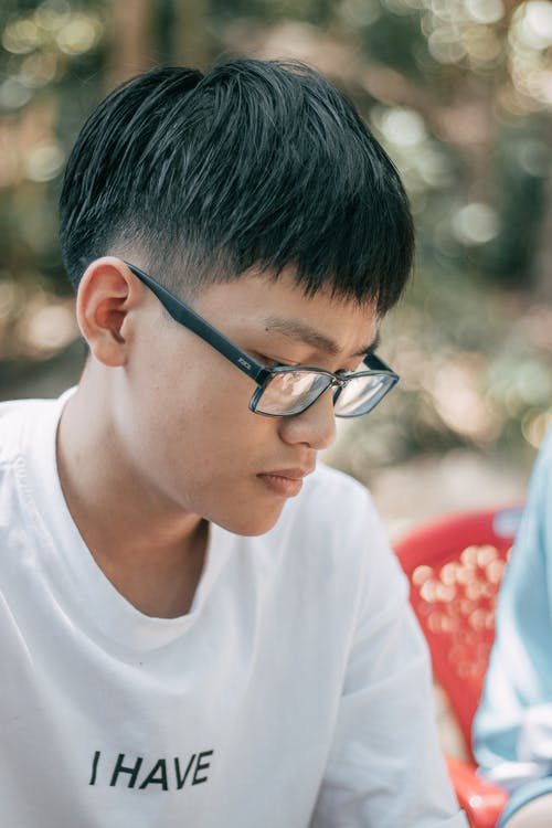 Handsome concentrated Asian teenager with dark straight hair in eyeglasses looking down in woodland on blurred background