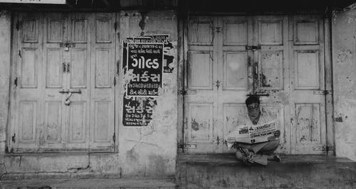 Man reading paper near decayed building