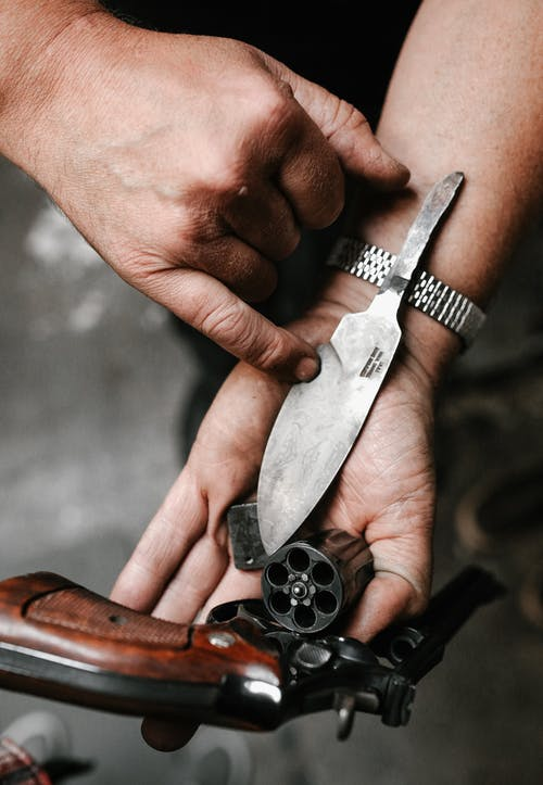 Person Holding Silver and Brown Pocket Knife