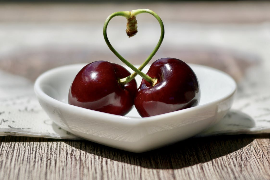 Two Cherry Fruits Knotted on Each Other on Heart Bowl
