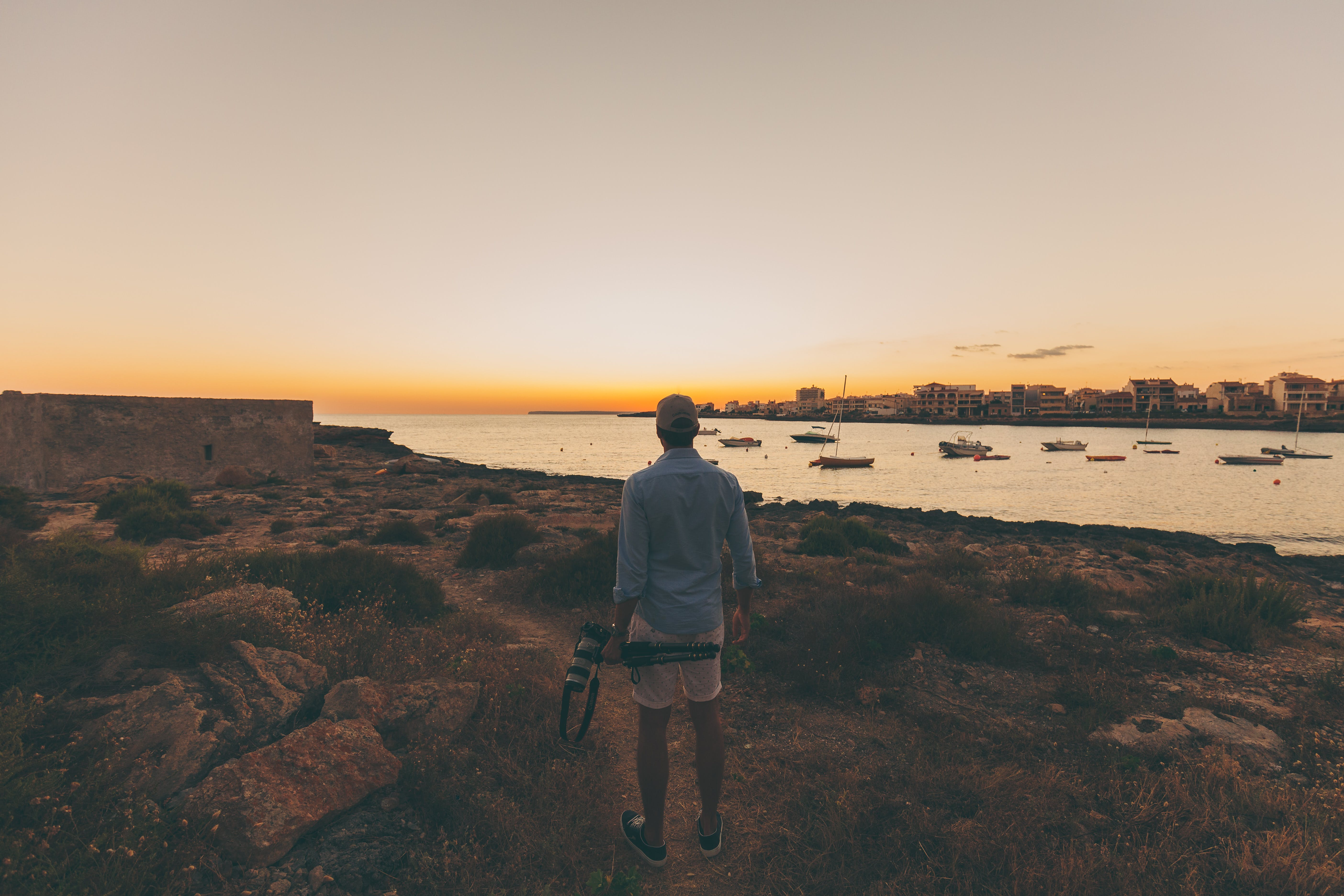 Man Standing on Pathway Near Rocks and Body of Water