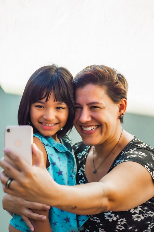 Happy middle aged woman hugging adorable Asian girl and taking selfie on mobile phone together