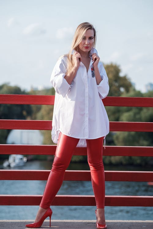 Full body of young confident female in high heeled shoes and white shirt standing on bridge over river and looking at camera