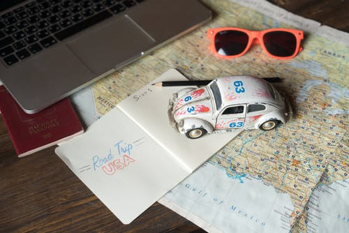 A White Toy Car on Top of the Notebook and Map