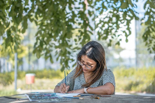 Serious young ethnic female artist in casual clothes and eyeglasses using paintbrushes while drawing picture in green park