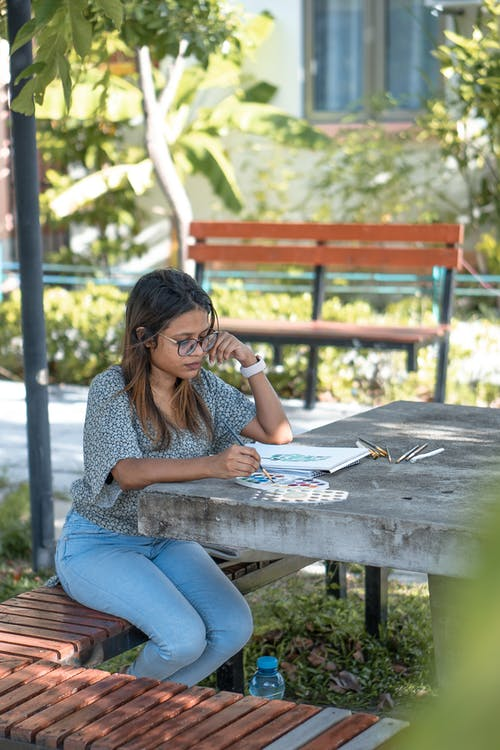 Serious young casual ethnic female painter in eyeglasses sitting on bench in park and drawing with watercolors and brushes