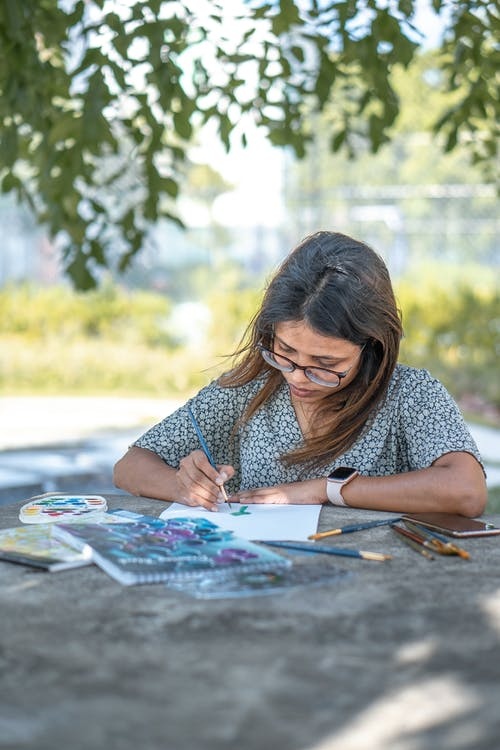 Young ethnic female painter drawing on paper in park