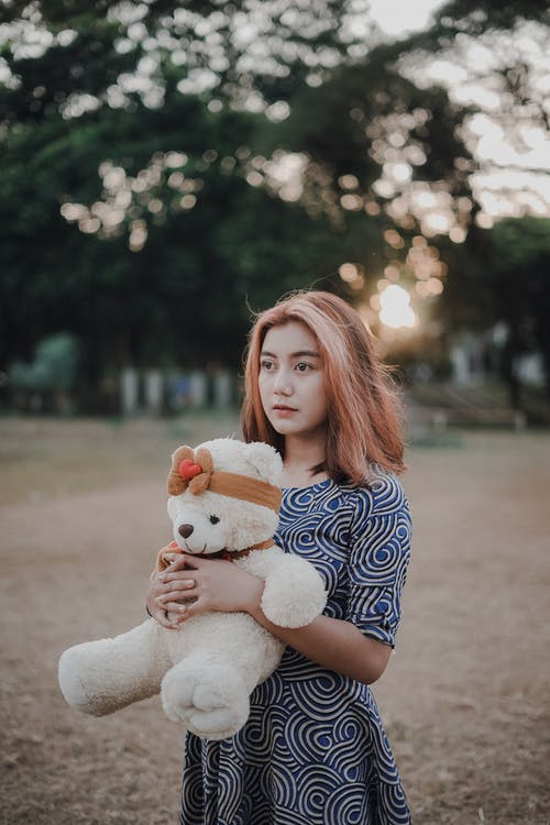 Woman in Blue and White Checkered Dress Holding White Bear Plush Toy