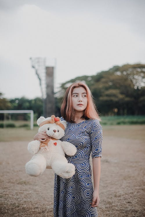 Woman in Blue and White Polka Dot Dress Holding White Dog Plush Toy